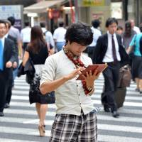 Social migration: A university student uses his tablet computer in Tokyo in June. Some social media users in the country say they are spending less time on Twitter or have quit for other services because it is too crowded and too difficult to use. | AFP-JIJI