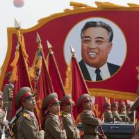 Marching on: Members of the North Korean military march past a portrait of Kim Il Sung during a parade commemorating the 65th anniversary of the Korea Worker's Party in Pyongyang in October 2010 | BLOOMBERG
