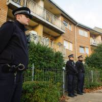 Seeking facts: Police officers stand outside apartment buildings in south London on Saturday as house-to-house enquiries are carried out in the area where three women were recently rescued from slavery. | AP