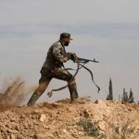 Close combat: A Shiite fighter clashes with members of the Sunni-dominated rebel Free Syrian Army in the town of Hatita, near Damascus, on Friday. In an attempt to halt the nearly 3-year-old civil war, Syria's government and opposition are likely to hold peace talks in Geneva in January, the United Nations announced Monday. | AP