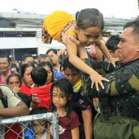 Out of order: Philippine military personnel prioritize women and children as people wait for evacuation flights out of the typhoon-stricken Philippine city of Tacloban on Tuesday | AP
