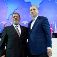 Happier times: Turkish Prime Minister Recep Tayyip Erdogan (right) and his guest, Egyptian President Mohammed Morsi, greet the audience during the congress of Erdogan's party in Ankara in September last year. | AFP-JIJI