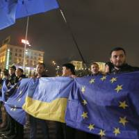 Party on hold: Activists wave Ukrainian and European Union flags during a night rally in support of Ukraine's integration with the European Union in the center of Kiev on Thursday, after its president-controlled parliament failed to pass any of a flurry of proposed bills allowing the release of jailed former Prime Minister Yulia Tymoshneko. | AP