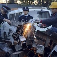 Grilled: Municipal police officers watch as a worker breaks down open-air barbecues confiscated over the past three months in Beijing's Xicheng district on Tuesday. | AP