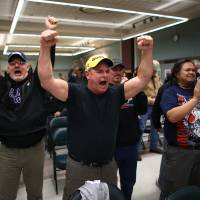 Up in arms: Boeing machinists celebrate in Seattle on Wednesday after voting to reject a contentious contract proposal that would have exchanged concessions for decades of secure jobs, at the city's International Association of Machinists union hall. The offer was rejected by 67 percent of those polled | AP