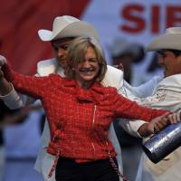 In the groove: Presidential candidate Evelyn Matthei dances with musicians during her closing campaign rally in Chillan, central Chile, on Thursday, the last day of campaigning for Sunday's election. The two leading candidates, Matthei and former President Michelle Bachelet, have an almost Shakespearean relationship as childhood friends whose fathers were top generals on opposite sides of Chile's deep political divide | AP