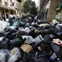Trashed: Trash fills a street during a strike by municipal workers in Santiago on Thursday. The workers started an indefinite strike in October to demand a pay raise, affecting dozens of municipalities, and on Thursday they extended it to more areas across the country, affecting various public services | AP