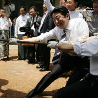 Taxing endeavor: Prime Minister Shinzo Abe plays tug-of-war with Myanmar schoolchildren at Lat Yat San Friends Elementary School in Yangon during a May visit to the Southeast Asian nation | AP