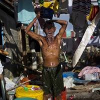 Water woes: A survivor of Typhoon Haiyan bathes in the ruins of his home in Guiuan, the Philippines, on Friday. Typhoon Haiyan, one of the most powerful storms on record, hit the country's eastern seaboard Nov. 8, leaving a wide swath of destruction. | AP