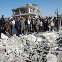 Cycle of violence: A picture released by Syria's official SANA news agency Monday shows people gathering around the crater caused by a car bomb in Thabitiyeh that killed six people. Fresh bomb attacks in Damascus and southern Syria killed at least 16 people on Wednesday | AFP-JIJI