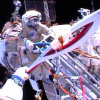 Olympic feat: Cosmonauts Oleg Kotov and Sergei Ryazanskiy (rear) perform a handoff of the Sochi 2014 Winter Olympic Games Torch during a spacewalk outside the International Space Station on Saturday. The torch also visited the ISS ahead of the 1996 Summer Games in Atlanta and the 2000 Olympic Games in Sydney, but this is the first time it has been along for a spacewalk | AFP-JIJI