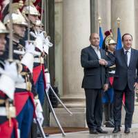 Turbulent ride: French President Francois Hollande (right) greets Tunisian President Moncef Marzouki upon his arrival at the Elysee Palace in Paris on Tuesday. Marzouki is in France for a two-day visit and was to address a UNESCO conference later Wednesday | AP