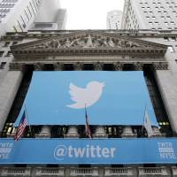 Takeoff: Twitter's corporate logo and other signage is draped across the front of the New York Stock Exchange on Thursday. Twitter set a price of $26 per share for its initial public offering Wednesday evening began trading Thursday under the ticker symbol 'TWTR,' in the most highly anticipated IPO since Facebook's 2012 debut | AP