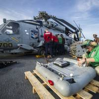 Mission of mercy: U.S. Navy sailors assigned to the Saberhawks of Helicopter Maritime Strike Squadron remove equipment from an MH-60R Sea Hawk helicopter aboard the aircraft carrier USS George Washington on Wednesday to make room for the transport of cargo and personnel to the Philippines to support humanitarian efforts in response to Typhoon Haiyan | AP