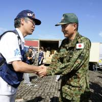 Where to start?: Dr. Joji Tomioka (left), deputy head of Japan's disaster relief team, greets Nobutoshi Nakanishi, the chief of the Self-Defense Forces' relief team, on Friday after the SDF team arrived in typhoon-stricken Tacloban in the Philippines | KYODO