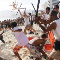 Seaside robbery: Municipal guards chase a gang of thieves that stole bags and wallets from people on Rio de Janeiro's Arpoador beach Wednesday. | AP