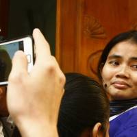 Freed, for now: Yorm Bopha (right), a government critic who has served more than a year in prison on charges widely condemned as trumped up, enters Cambodia's Supreme Court in Phnom Penh on Friday for a hearing. The court released Yorm Bopha on bail the same day and sent her case back to the Appeals Court for further investigation and a possible retrial. | AP