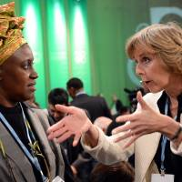 Pushing for change: EU Commissioner for Climate Action Connie Hedegaard (right) talks with Alice Akinyi Kaudia from Kenya prior to the opening of the high-level segment of the U.N. Climate Change Conference in Warsaw on Nov. 19. | AFP-JIJI