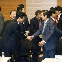 Shake on it: Japanese and South Korean lawmakers working to promote bilateral ties shake hands Saturday in Tokyo after issuing a statement urging their governments, together with China, to produce joint Northeast Asian history textbooks. | KYODO