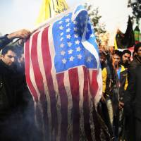 Iranian protesters burn a U.S. flag during an anti-American rally in Tehran on Nov. 4.  Iranian officials said Sunday the country made progress with world powers during 'serious' talks over Tehran's nuclear program, but insisted the nation cannot be pushed to give up uranium enrichment. | AP