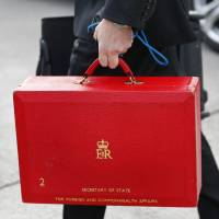 Red alert: A staff member carries a case for British Foreign Secretary William Hague after his arrival Saturday at Geneva International Airport for talks on Iran's nuclear drive. | AP