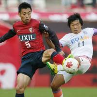 Too close for comfort: The Antlers' Takeshi Aoki (left) and Sanfrecce's Hisato Sato vie for the ball during an Emperor's Cup match on Saturday. Hiroshima beat Kashima 3-1 | KYODO