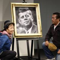 Eternal flame: A Japanese couple pose with a portrait of the late U.S. President John F. Kennedy at a memorial venue specially set for his Japanese fans in Tokyo on Friday, to pay their respects to mark the 50th anniversary of his assassination. | AP