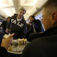 Sweet touch: U.S. Secretary of State John Kerry offers cupcakes to members of the press traveling with him from Washington to the Middle East on Saturday. Kerry was in Cairo on Sunday to press for reforms in the highest-level American visit to Egypt since the ouster of the country's first democratically elected president | AP