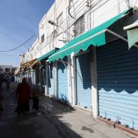 Not good for business: People walk past closed shops in Tripoli on Saturday, before local authorities announced a 'three-day general strike in all public and private sectors starting November 17' to protest violence | AFP-JIJI