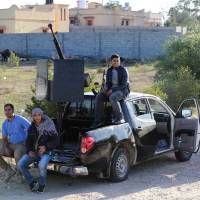 Need a ride?: Members of the Tripoli Rebels Brigade militia patrol a road in Tajura on Saturday after foiling attempts by Misrata-based militiamen to advance into the city earlier in the day. | AFP-JIJI