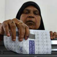 Third time's the charm: A voter casts her ballot at a polling station in Male on Saturday as the Maldives began its third bid to choose a president and end unrest sparked by the toppling of its first freely elected leader 21 months ago | AFP-JIJI