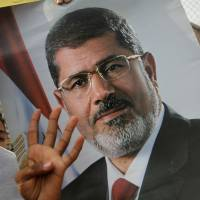 Have Morsi: Supporters of Egypt's ousted President Mohammed Morsi raise his poster and a hand with four raised fingers, which has become a symbol of the Rabaah al-Adawiya mosque, where Morsi supporters had held a sit-in for weeks that was violently dispersed in August, during a protest Nov. 8 in Cairo | AP