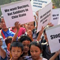 Starting young: Children display placards as Ethnic Chin refugees from Myanmar participate in a protest against alleged discrimination and repression by their government, in New Delhi on Wednesday. A boat carrying around 70 Rohingya asylum seekers sank off Myanmar's coast Sunday | AFP-JIJI