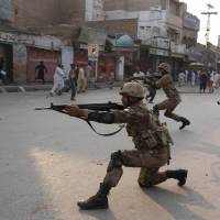 Taking a stance: Pakistani soldiers take position to disperse Sunni Muslims protesting against an attack on a Sunni mosque and seminary in Multan on Saturday. Pakistan imposed a curfew the same day in the city of Rawalpindi, where sectarian clashes killed eight people and injured at least 35 | AFP-JIJI