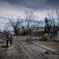 Desperation: Typhoon victims walk through land ravaged by Typhoon Haiyan in Tacloban, on the eastern island of Leyte, on Wednesday. | AFP-JIJI