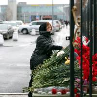 In remembrance: A woman lays flowers at a list of the plane crash victims at the international airport in Kazan on Monday. A Boeing 737 operated by a Russian airline crashed there the previous day while attempting to land, killing all 50 on board. | AFP-JIJI