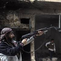 One shot: A Free Syrian Army fighter fires his weapon in Aleppo on Nov. 16. | REUTERS/KYODO
