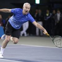 You cannot be serious: Seven-time grand slam singles champion John McEnroe plays a shot during his charity match against Kei Nishikori in Tokyo on Sunday | AP
