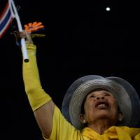 Taking a stand: An opposition protester waves the Thai flag during a rally against an amnesty bill at Democracy Monument in Bangkok on Monday | AFP-JIJI