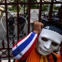 Faceless in a crowd: An antigovernment demonstrator stands by a barricade put up by a riot squad at police headquarters in Bangkok on Thursday. Thai Prime Minister Yingluck Shinawatra called on demonstrators seeking her ouster to end their occupation of government buildings and enter negotiations for the good of the nation. | BLOOMBERG