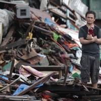 Surveying the damage: A resident looks at houses damaged by Typhoon Haiyan in Tacloban city, in the central Philippines' Leyte province, on Sunday. Haiyan, one of the most powerful typhoons ever recorded slammed into the country's center Friday leaving a wide swath of destruction and scores of people dead | AP