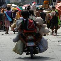 Destructive behavior: Residents carry looted goods on a motorbike in Tacloban city, Leyte province, central Philippines, on Sunday after Typhoon Haiyan hit the city Friday. | AP