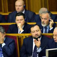 Cacophony: Ukrainian government ministers listen as Prime Minister Mykola Azarov (right) address pro-European opposition lawmakers in parliament in Kiev on Friday. Azarov's administration is under fire for missing what some see as a historic opportunity to join the European Union by caving in to Russian pressure. | AFP-JIJI