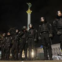Holding the line: Ukrainian riot police seal off Independence Square in central Kiev on Saturday night. Police broke up a large anti-government demonstration in the city before dawn with truncheons and tear gas, in clashed that injured many protesters. | AP