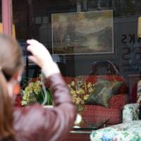I wuz here: A woman looks at a 'vandalized' painting by British artist Banksy in a window at Housing Works' Gramercy thrift shop Wednesday. | AFP-JIJI