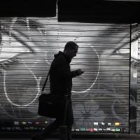Eyes on you: A man uses a cellphone in central Madrid on Thursday. Spy agencies in Spain, Germany, France and Sweden are carrying out mass surveillance of online and phone traffic in collaboration with Britain, The Guardian newspaper reported Friday. | AP