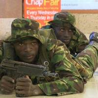 Down low: Kenyan troops take up positions inside Nairobi's Westgate Mall on Sept. 21 after Somali militants attacked the upscale shopping complex. | AFP-JIJI
