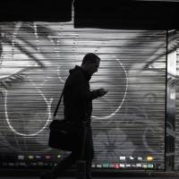 A man looks at his cellphone as he walks in downtown Madrid on Thursday after allegations emerged that Spain was a target for surveillance by the NSA. | AP