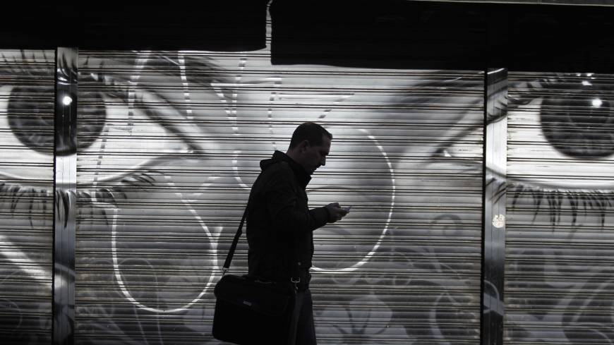 A man looks at his cellphone as he walks in downtown Madrid on Thursday after allegations emerged that Spain was a target for surveillance by the NSA.