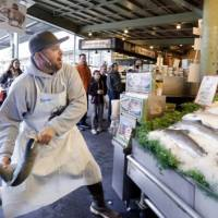 Natural taste: Scott Smith tosses a fresh salmon to a colleague behind the counter at the Pike Place Fish Market in Seattle in October 2010. Television ads featuring Pike Place fishmongers, organic farmers and others have hammered the proposal to label food produced with genetic engineering. | AP